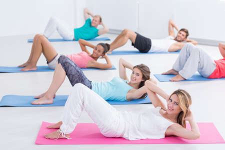 in unison: Group of young people training together and doing the sit-ups