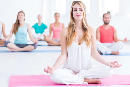 in unison: Group of young people sitting concentrated on yoga class