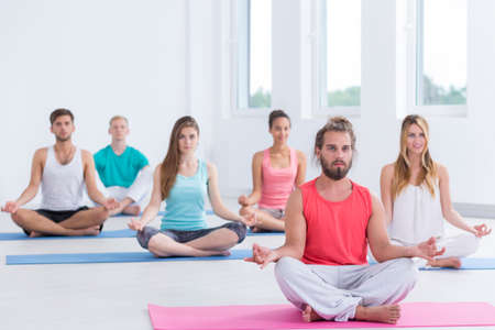in unison: Group of yoga practitioners sitting cross legs on the floor