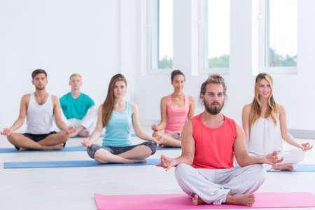 cross legs: Group of yoga practitioners sitting cross legs on the floor