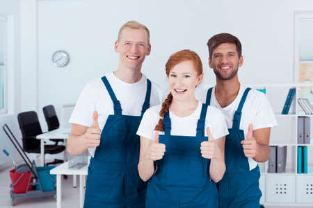 Happy team of professional cleaners standing in a light office