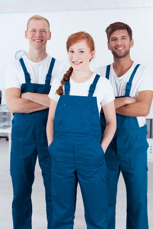 service man: Image of a happy three professional cleaners wearing uniforms Stock Photo