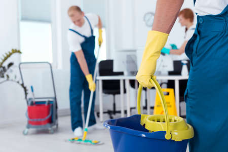 Image of person holding mop pail and man cleaning floor Stock Photo