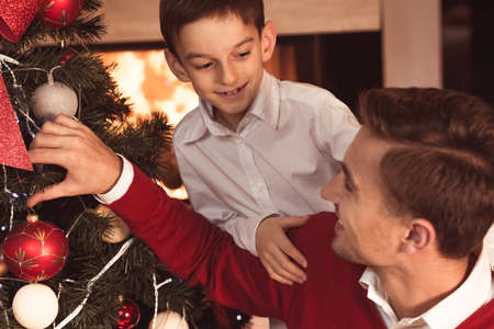 decorating christmas tree: Happy father and son decorating Christmas tree