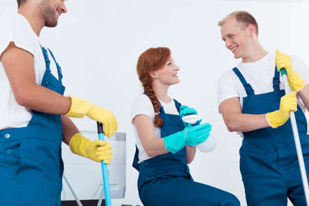 Picture of happy professional office cleaners having break at work