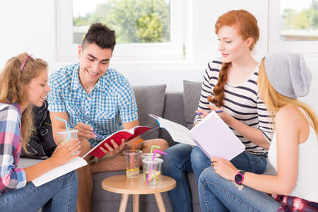 free education: Young man explaining the topic to his friends keeping the notebooks