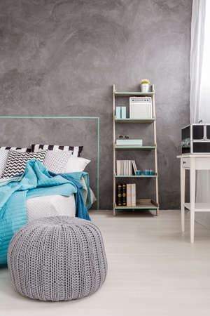 bedcover: Shot of a minimalist bedroom interior with a modern grey pouf Stock Photo