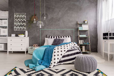 bedcover: Cropped shot of a comfortable interior with grey walls and black and white rug