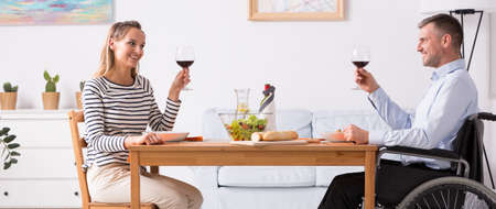 Woman sitting in front of her disabled husband and making a toast Stock Photo