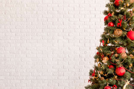 white christmas tree: Traditional Christmas tree on a white brick wall background