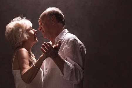 Senior couple dancing - isolated on dark background