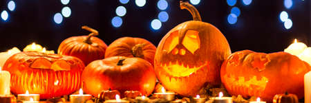 Pumpins lanterns for Halloween, lying on tha table and illuminated by candles
