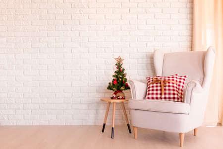 Einfache Weihnachten Wohnzimmer mit Sessel und kleinen Weihnachtsbaum Standard-Bild