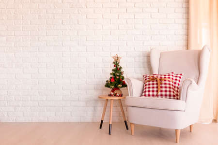 Simple Christmas living room with armchair and small Christmas tree Banco de Imagens