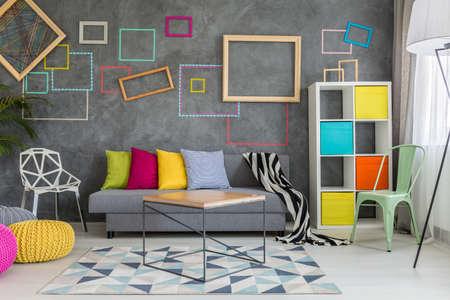 Ruim appartement in grijs met kleurrijke muurdecoratie en bank