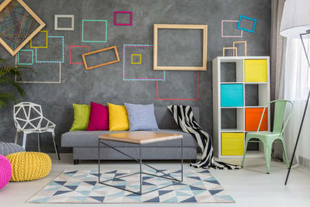 wall decor: Spacious apartment in grey with colorful wall decor and sofa
