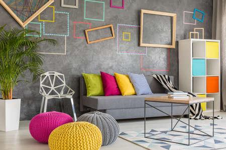 Colorido salón con pared gris decorativos y pufs de lana Foto de archivo