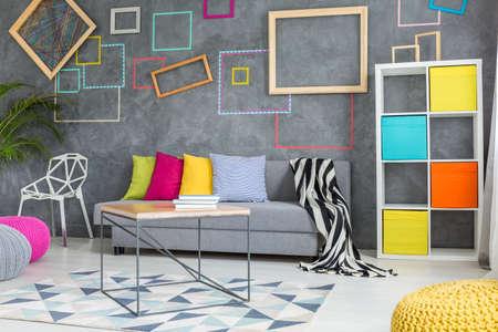 Habitación gris con paneles de pared decorativos, sofá y mesa de madera