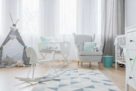 Shot of a bright babys room with a little tent and a rocking horse
