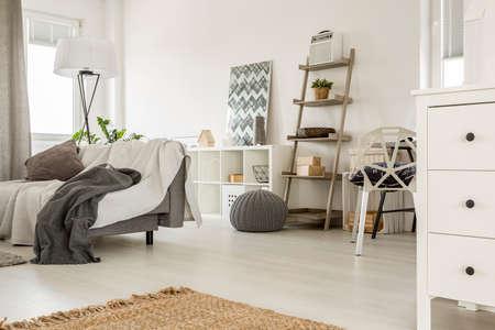 Ampio interni interni in bianco con divano e mobili in legno