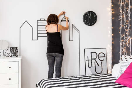 wall decoration: Woman making DIY wall decoration in her bedroom Stock Photo
