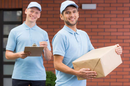 courier: Delivery man holding a package, young courier with a clipboard Stock Photo