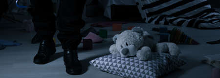 thievery: Burglar standing in child room with pillow and teddy bear on the floor