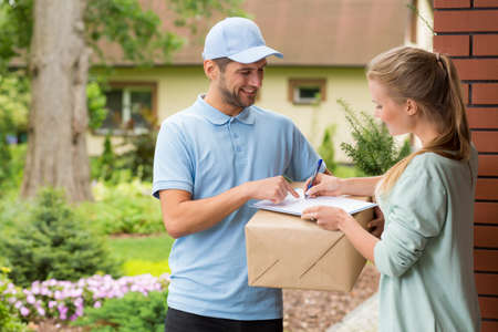 Young courier holding a parcel, woman signing a delivery form