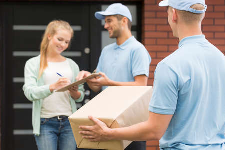 courier: Professional courier  holding a package, in the background woman signing a form for a courier