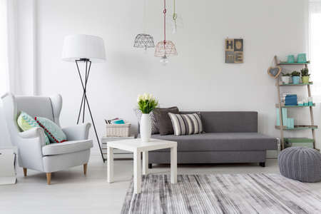cosy: Shot of a modern living room interior with a classic grey armchair Stock Photo