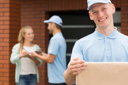 courier: Happy courier holding a package, in the background woman signing a form for a courier Stock Photo