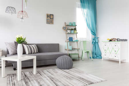 asleep chair: Grey living room with a mint curtains and white walls