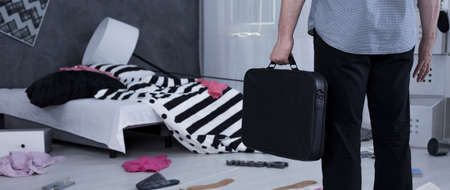 Man standing with the suitcase in front of demolished room Stock Photo