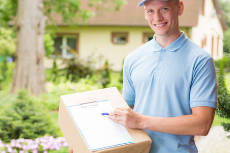 courier: Young, happy courier holding a parcel and a clipboard