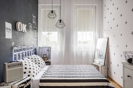 Shot of a small black and white bedroom with a big bed and two windows