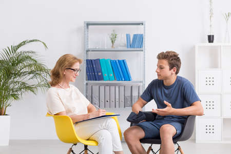 female therapist: Female therapist talking with teenage boy about his problems Stock Photo