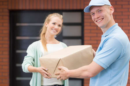 courier: Happy young courier delivering a parcel to a nice customer