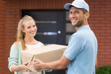 Happy young courier delivering a package to a nice woman