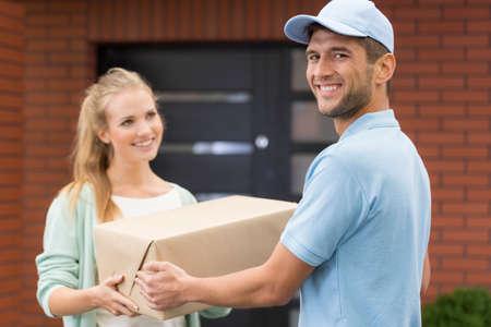 Gelukkig jong koerier leveren van een pakket om een mooie vrouw Stockfoto