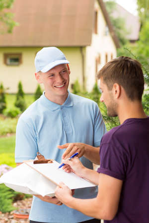 courier: Happy courier and young man signing a delivery form Stock Photo