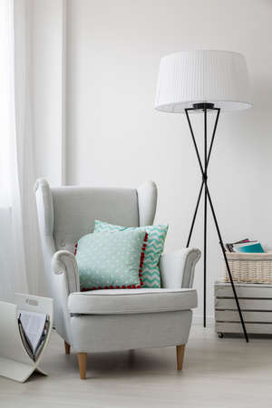 elegant design: Cropped shot of a stylish grey armchair and a floor standing lamp
