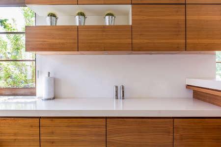 Unità di cucina in legno e piano di lavoro bianco in interni moderni Archivio Fotografico