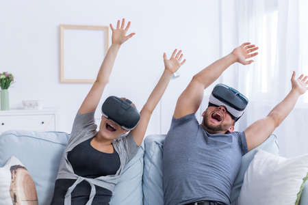 Young man and woman wearing VR glasses having fun with a virtual roller coaster 스톡 콘텐츠