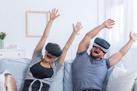 Jonge man en vrouw die VR-glazen dragen met plezier met een virtuele achtbaan Stockfoto