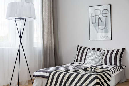 Light bedroom with floor lamp, window and pattern bedding