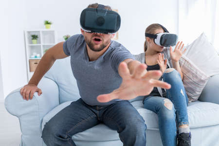 Man and woman wearing VR glasses, excited man trying to catch something
