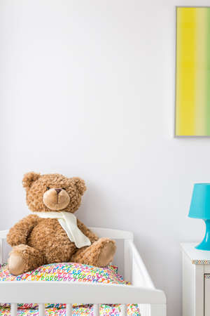bright paintings: View of a sweet teddy bear in a cradle in baby room Stock Photo