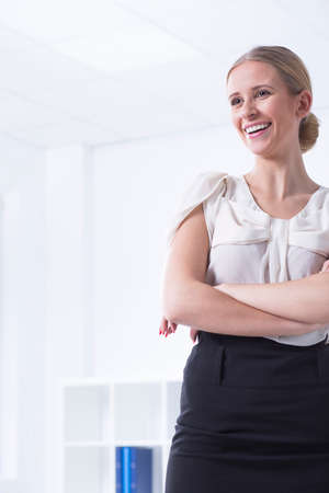 communicative: Elegant woman standing with folded arms at the office interior and smiling