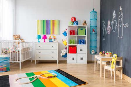 Geräumige bunte Kinderzimmer mit Wiege und Tafel Wand Standard-Bild