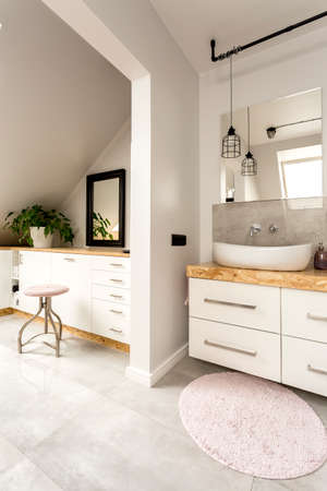 interior lighting: Bright interior of an attic bathroom with minimalistic lighting, white chest of drawers, mirror and modern amenities